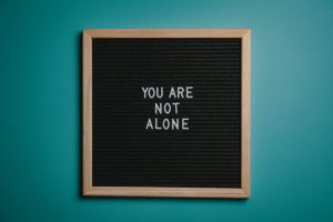 you-are-not-alone-quote-board-on-brown-wooden-frame-2821220